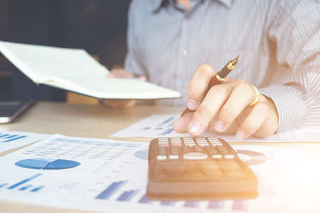 Business man or accountant working Financial investment on calculator with calculate Analyze business and market growth on financial document data graph and writing ,Accounting,Economic,commercial.