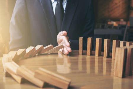 倒れた実業家の手から連続的な落下を停止する木製ドミノ効果のクローズ アップやリスク、戦略、ビジネス成功介入の考え方。