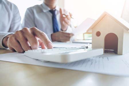 El hombre firma una póliza de seguro de vivienda para préstamos hipotecarios, el Agente tiene documentos de gráficos de la tabla de inversión de préstamos y el pago de la tabla de cálculo, concepto de bienes raíces.