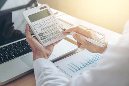Female accountant calculations and analyzing financial graph data with calculator and laptop Business, Financing, Accounting, Doing finance, Economy, Savings Banking Concept. Standard-Bild