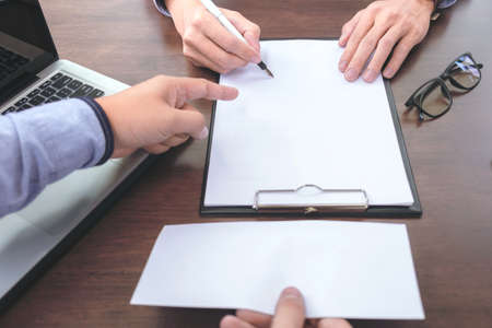 Close up of the hand employer focus the employee to write a letter of resignation and filing final remuneration, resign concept.