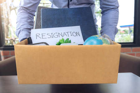Businessman carrying packing up all his personal belongings and files into a brown cardboard box to resignation, resign concept.
