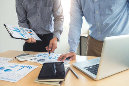 reviews: Co working conference, Business team meeting present, investor colleagues discussing new plan financial graph data on office table with laptop and digital tablet, Finance, accounting, investment. Stock Photo