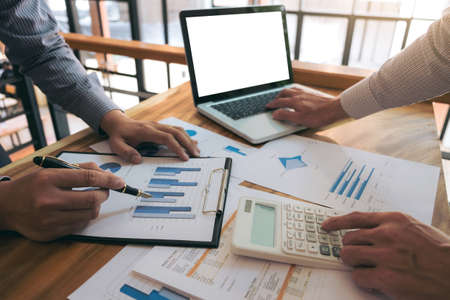 reviews: Co working conference, Business team meeting present, investor colleagues discussing new plan financial graph data on office table with laptop and calculator, Finance, accounting, investment. Stock Photo
