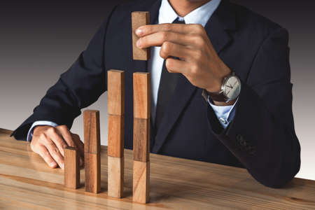 Businessman hand arranging stacking wooden blocks development as step stair, Business growth success process, Growth concept with wooden blocks, plan and strategy in business. Stock Photo