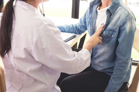 Professional examining, Female doctor using a stethoscope to listen to women patient's chest checking heartbeat or lung in medical clinic, Physical examination, Medical and health care concept.