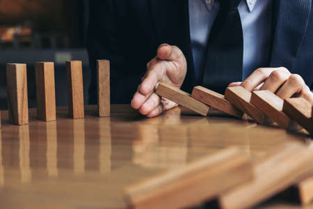 Close up of businessman hand Stopping Falling wooden Dominoes effect from continuous toppled or risk, strategy and successful intervention concept for business. Stock Photo