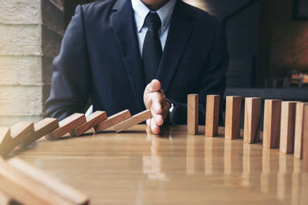 Close up of businessman hand Stopping Falling wooden Dominoes effect from continuous toppled or risk, strategy and successful intervention concept for business. Stockfoto