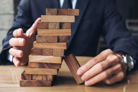 木製ゲーム代替リスクの概念、計画、事業戦略、知的な青年実業家を上げる、幹部の手を維持、共同管理塔のウッド ブロック。