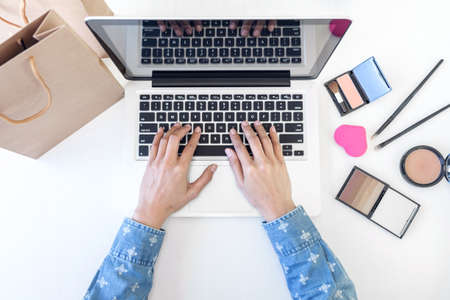 Makeup and beauty blog, elegant female fashion blogger working with a laptop, many cosmetics and teaching online tutorial.