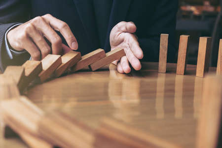 Close up of businessman hand Stopping Falling wooden Dominoes effect from continuous toppled or risk, strategy and successful intervention concept for business. 版權商用圖片