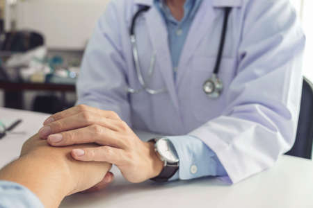 Close up of doctor touching patient hand for encouragement and empathy on the hospital, cheering and support patient, Bad news, medical examination, trust and ethics. Stock Photo