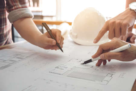 Image of engineer or architectural project, Close up of Architects engineers hands drawing plan on BluePrint and discussing to partner with Engineering tools on workplace, Construction concept.