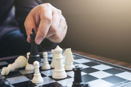 pensamiento estrategico: Close up of hands confident businessman colleagues playing chess game to development analysis new strategy plan, leader and teamwork concept for success.