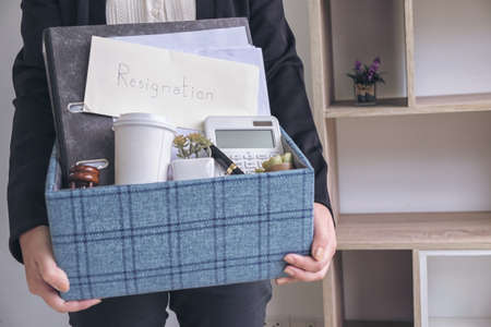 business woman carrying packing up all his personal belongings and files into a brown cardboard box to resignation in modern office, resign concept. Banco de Imagens