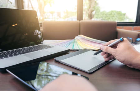Creative creativity graphic designer working with graphics tablet,laptop and smart phone, colour chart at workplace on wooden desk , colour ideas style concept.