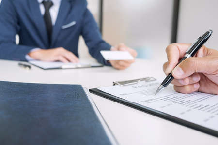Interviewer or Board reading a resume during job interview, Employer interviewing a young male job seeker for recruitment talking in modern office and filing card, employment and recruitment concept.