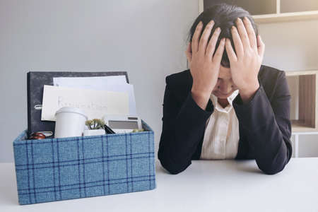 Images of packing up all her personal belongings and files into a brown cardboard box and Business woman has stress to resignation in modern office, resign concept. Banco de Imagens