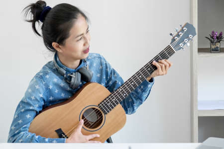 social media learning concept, relaxing and playing guitar, Young woman concentrating learn and play the guitar to a tutorial on lesson online, while she recording music video in camera at home.