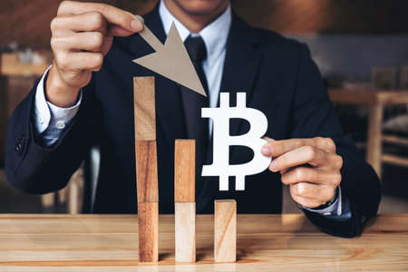 Business Economic crisis concept, Businessman holding showing bitcoin symbol, concede decrease of price and Depression of the economy. wooden block of the financial crisis of income in bitcoins.