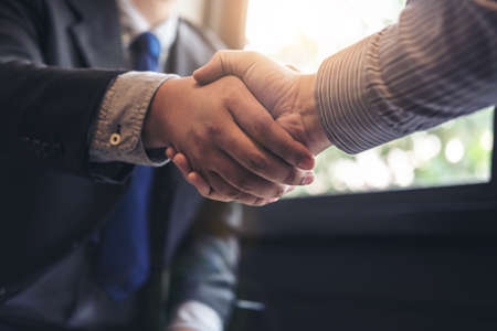 Two business men shaking hands during a meeting to sign agreement and become a business partner, enterprises, companies, confident, success dealing, contract between their firms.