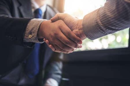 Dwaj biznesmeni ściskają dłonie podczas spotkania, aby podpisać umowę i zostać partnerem biznesowym, przedsiębiorstwami, firmami, pewnymi siebie, odnoszącymi sukcesy kontraktami między swoimi firmami.