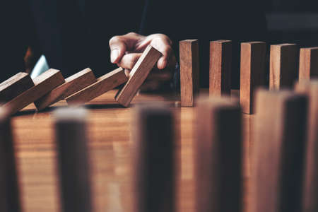 Close up of businessman hand Stopping Falling wooden Dominoes effect from continuous toppled or risk, strategy and successful intervention concept for business. Archivio Fotografico