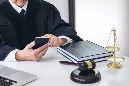 Male lawyer or judge working with smart phone and scales of justice, Law books, gavel, report the case on table in modern office, Law and justice concept.