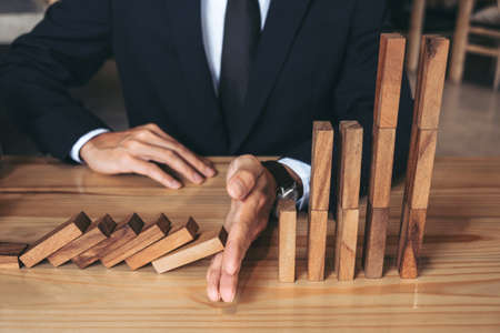 Close up of businessman hand Stopping Falling wooden Dominoes effect from continuous toppled or risk, strategy and successful intervention concept for business. Stock fotó