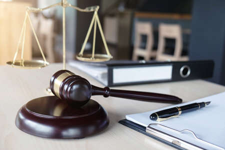 Close up of gavel and scales of justice and Report the case with paper on wooden table in office, Law and justice concept.