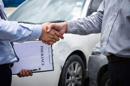 Insurance Agent and customer shaking hands, Traffic Accident and insurance concept.