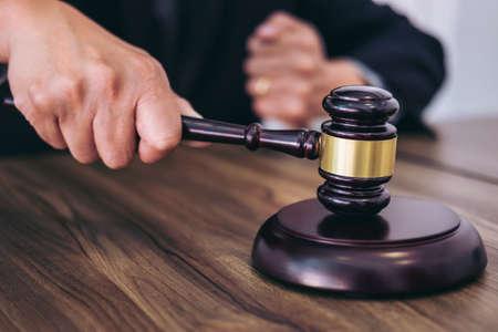 Männliche Rechtsanwalt- oder Richterhand, die den Hammer auf klingendem Block, arbeitend am Gerichtssaal, Gesetzes- und Gerechtigkeitskonzept schlägt.