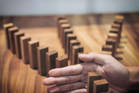 Risk and strategy in business, Close up of businessman hand stopping wooden block between three way from falling in the line of domino. Banque d'images