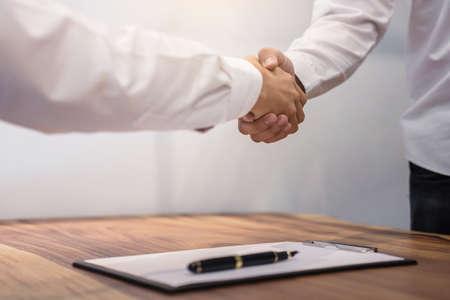Immobilienmakleragent und -kunden, die Hände rütteln, nachdem Vertragsdokumente für Grundstückskauf unterzeichnet worden sind, Bankangestellte gratulieren, Konzepthypothekenkreditgenehmigung.