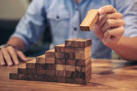 Concepto de riesgo alternativo, plan y estrategia en los negocios, riesgo de hacer el concepto de crecimiento empresarial con bloques de madera, la mano del hombre se ha acumulado y apilando un bloque de madera.
