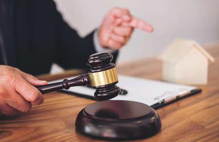 Homme avocat ou juge de la main frappe le marteau sur le bloc sonore, travaillant à la salle d'audience pour décider d'assurance habitation, le concept de droit et de la justice, régler une maison traitant de la poursuite.