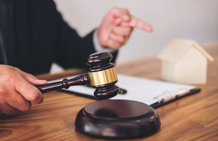 Male lawyer or judge hand's striking the gavel on sounding block, working at courtroom for decide home insurance, Law and justice concept, Settle a house dealing lawsuit. Archivio Fotografico