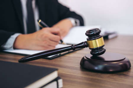 Gavel on wooden table and Lawyer or Judge working with agreement in Courtroom theme, Justice and Law concept. 版權商用圖片 - 89633890