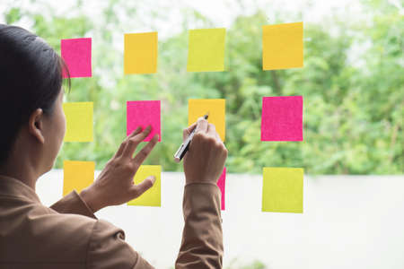 Young creative professional leader using post it notes in glass wall to writing strategy business plan, management and people concept.