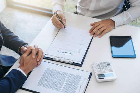 Der Geschäftsmann wird eine Kfz-Versicherung unterschreiben, der Agentenmann hält das Dokument und wartet, bis seine Antwort abgeschlossen ist.
