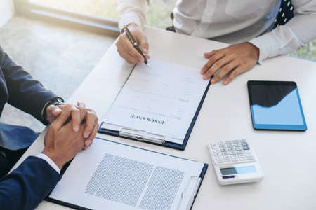 Businessman will be signing a car insurance policy, Agent man is holding the document and waiting for his reply to finish. Archivio Fotografico