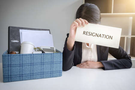 Images of packing up all her personal belongings and files into a brown cardboard box and Business woman has stress to resignation in modern office, resign concept. Stockfoto