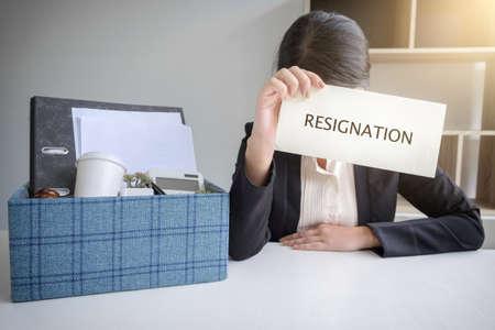 Imágenes de empacar todas sus pertenencias personales y archivos en una caja de cartón marrón y Mujer de negocios tiene estrés a la resignación en la oficina moderna, renunciar concepto. Foto de archivo