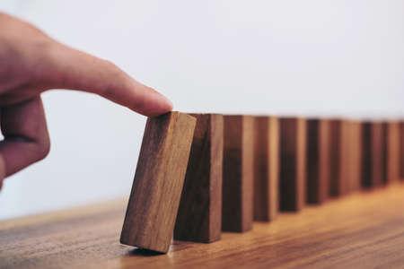 Risiko und Strategie im Geschäft, Abschluss des Geschäftsmannhandspielens, das Stoßholzblock auf einer Linie des Dominos beginnt.