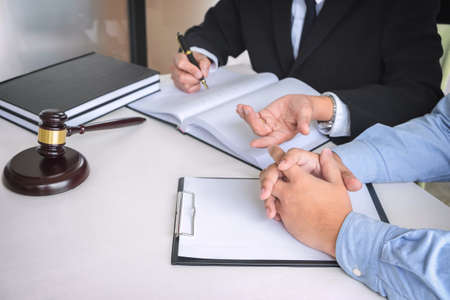 Close up of gavel, Male lawyer or judge Consult with client and working with Law books, report the case on table in modern office, Law and justice concept.