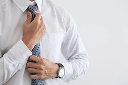 若い魅力的なビジネスマンのクローズアップは、グレーのネクタイを着用し、ネクタイを調整します。