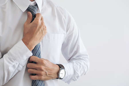 Close up of Young attractive businessman wears a gray tie and adjusting tie. Stock Photo - 89664834