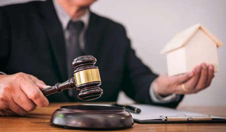 De mannelijke advocaat of rechterhand slaat de hamer op klinkend blok, werkend in rechtszaal voor beslis huisverzekering, Wet en rechtvaardigheidsconcept, regel een rechtszaak. Stockfoto