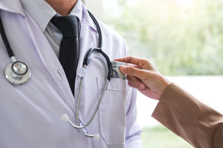 Doctor received corruption money from patient, hand putting money in doctor pocket form of dollar banknotes, Bribery and corruption in Health Care Industry.