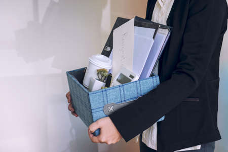 business woman carrying packing up all his personal belongings and files into a brown cardboard box to resignation in modern office, resign concept. Archivio Fotografico